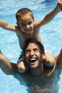 A father and son in a pool.